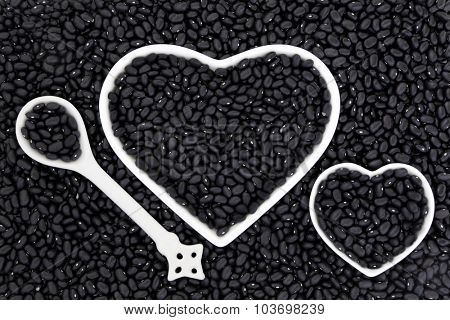 Black bean super health food in porcelain heart shaped dishes and spoon forming an abstract background.