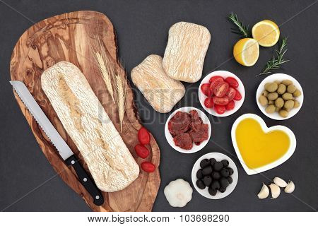 Mediterranean food with olives, fresh and sun dried tomatoes, garlic, lemon, oil and ciabatta bread on olive wood board with wheat sheaths and rolls.