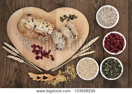 Cranberry seed bread on heart shaped board with wheat and sheaths, sunflower and pumpkin seeds, oatmeal  and dried cranberries over old oak background.