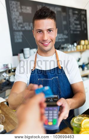 Man holding credit card reader at cafe