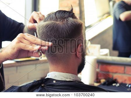 back view of man in barber shop. barber cutting hair with scissors