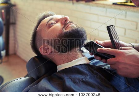 barber shaving beard with electric razor and holding comb in barbershop