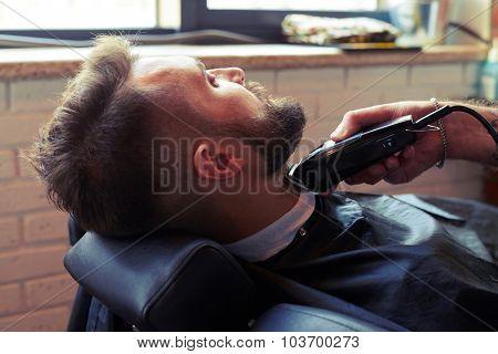 barber shaving beard with electric razor in barber shop