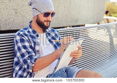 smiley bearded man sitting on bench and writing in notepad at outdoors
