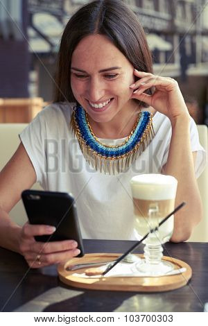 smiley young woman sitting in cafe and looking at smartphone