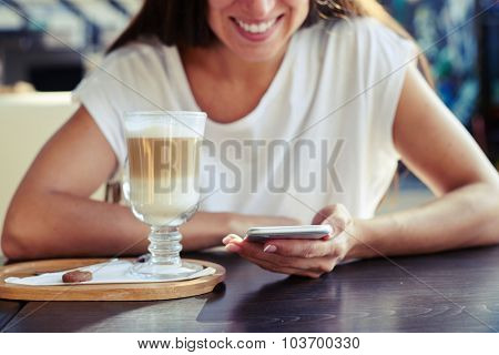 portrait of smiley young woman sitting in cafe with smartphone and cup of cappuccino