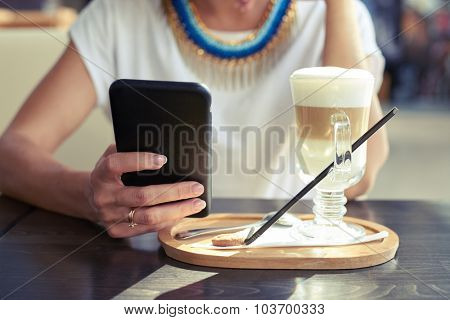 close up photo of woman using smartphone in cafe. focus on the hand