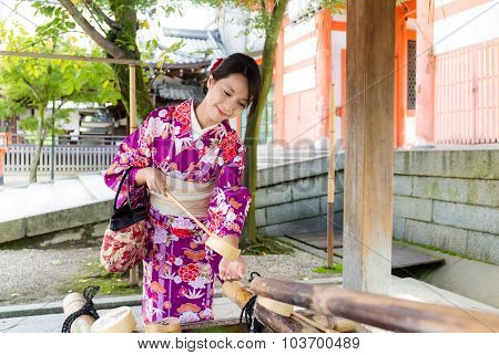 Japanese woman using the water bamboo ladle for purification