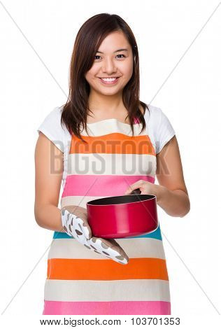Asian young housewife cooking with saucepan and cotton gloves