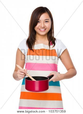 Asian housewife cooking with saucepan