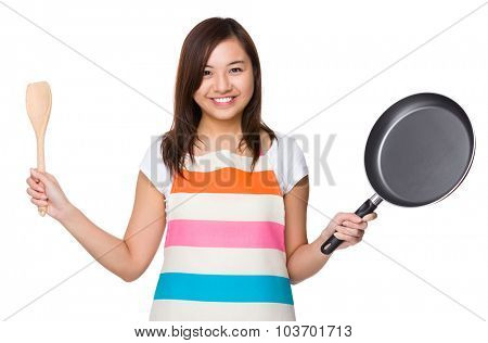 Asian Housewife holding up with frying pan and wooden ladle