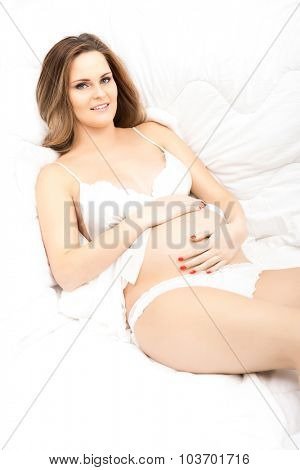Pretty pregnant woman in a bed