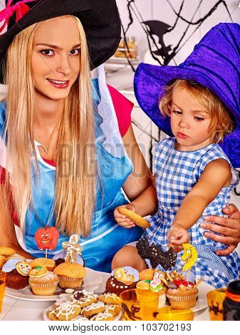 Mother with daughter preparing halloween cake.