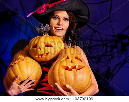 Happy witch holding three pumpkins