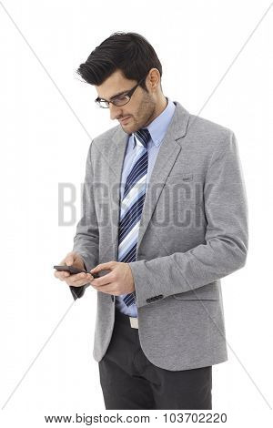 Young businessman using mobilephone, dialing.
