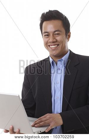 Closeup portrait of happy Asian businessman, looking at camera, holding laptop computer in hand.