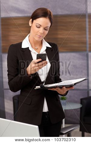 Businesswoman using mobilephone holding organizer, standing in office.