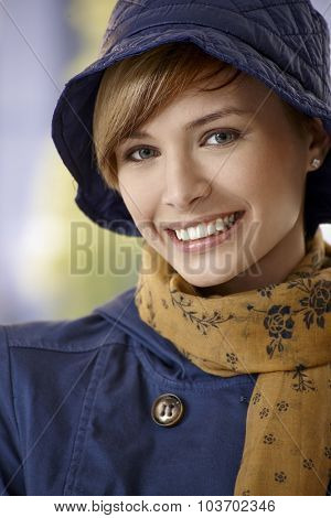 Closeup portrait of beautiful young woman wearing autumn clothes, smiling.