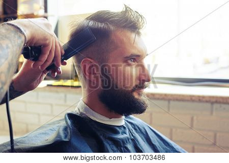 barber cutting hair with electric clipper and comb in a barber shop