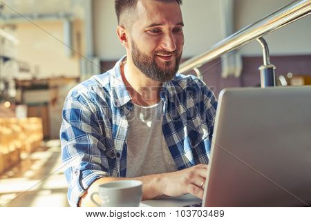 smiley man working with laptop in cafe