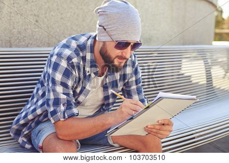 stylish bearded man sitting on bench and writing in notepad at outdoors