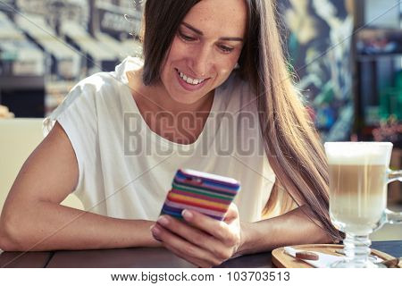 young smiley woman looking at her smartphone in the cafe