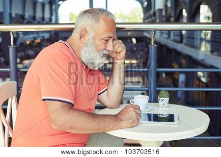middle-aged man with cup of coffee and tablet pc resting in cafe