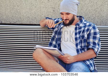 thoughtful stylish man sitting on bench and looking at his notepad at outdoor