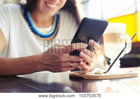 smiley woman using smartphone in cafe. focus on the hand