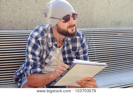 outdoor portrait of thoughtful man holding notepad and looking at something