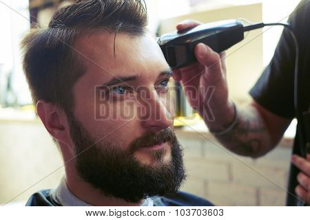 barber cutting hair with electric clipper in a barber shop