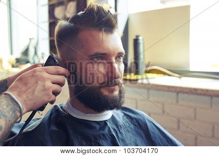 portrait of handsome man with beard in barbershop. barber working with electric razor