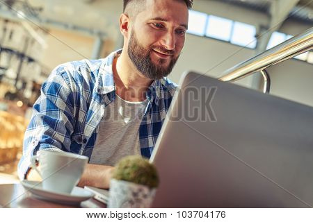 cheerful man having coffee break and working with laptop in cafe