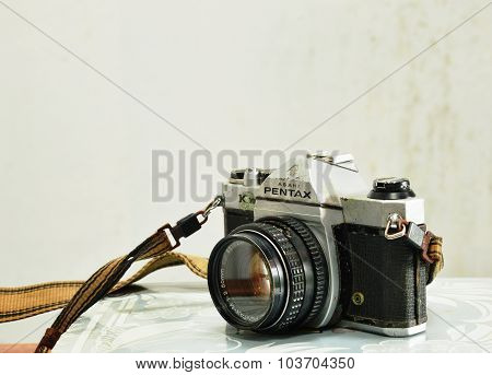 Model of Pentax K 1000 film camera on photo album