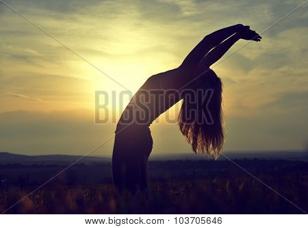Silhouette of young woman stretching on a meadow at sunset
