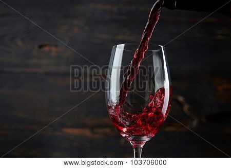 Pouring red wine into the glass against dark wooden background