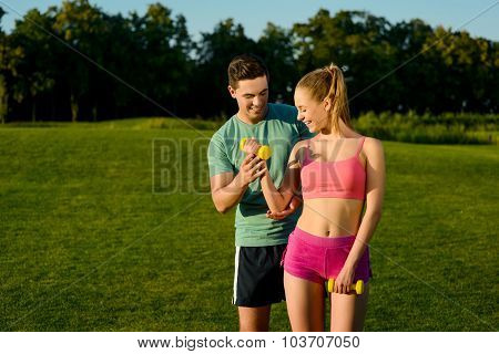 Sports trainer engaged in sports with a girl in the park.