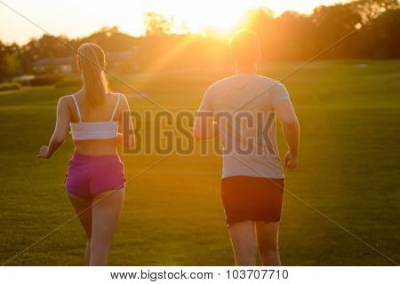 Guy and a girl running in the park.