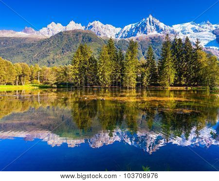 The mountain resort of Chamonix.  City Park is illuminated by the setting sun. The lake reflected the snow-capped Alps and evergreen spruce