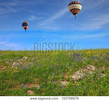 Two beautiful balloons fly over flowering field. Flowering Golan Heights on sunny day
