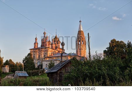 Evening Rural Landscape With Old Church And Wooden Houses