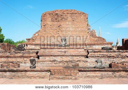 Temple Ruins And Damaged Buddha Statue At Wat Mahathat, Ayutthaya, Thailand