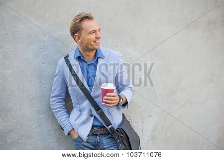 Man standing by the wall and smiling
