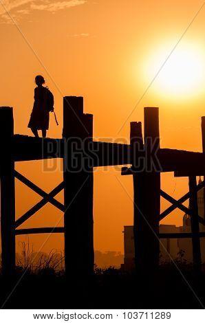 Girl on U bein bridge at sunset, Taungthaman lake, Amarapura, Burma.