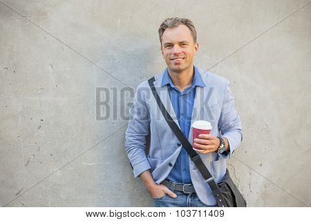 Man standing by the wall with a cup in his hands