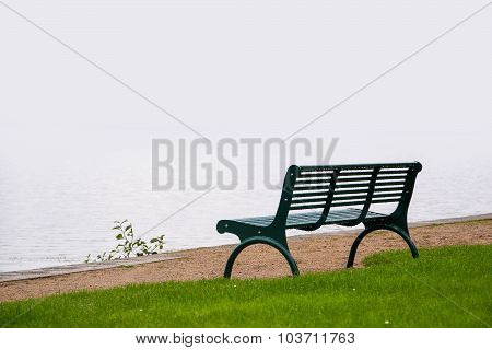 Empty Park Bench, Wet From The Rain On The Shore Of A Misty Lake