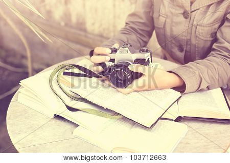 Girl Hands With Old Style Camera And Book Outdoor