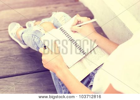 Schoolgirl Sitting On Floor And Wrote In A Notebook