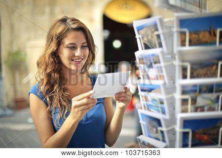 Happy woman choosing a postcard