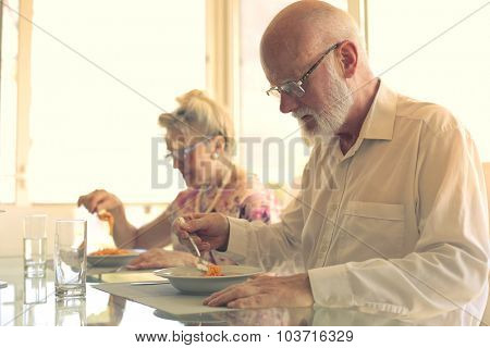 Elderly couple eating together